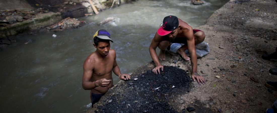 Hombres buscando entre los restos que sacaron del fondo del contaminado río Guaire en busca de trozos de oro o cualquier cosa de valor.