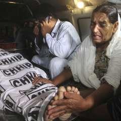 La madre de un agente de policía, que fue asesinado por un pistolero, llora junto al cuerpo de su hijo, trasladado en ambulancia a un hospital de Karachi, en Pakistán. Foto: AP