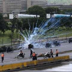 Fuegos artificiales lanzados por manifestantes antigubernamentales explotan cerca de las fuerzas de seguridad que circulan en motocicletas en Caracas. Foto: AP