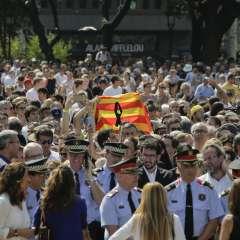 Una multitud de personas, entre las que sobresale una bandera de Cataluña con un crespón negro, se reúnen para guardar un minuto de silencio en memoria de las víctimas del ataque extremista en Las Ramblas, Barcelona, el 18 de febrero de 2017. Foto: AP