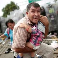 Un migrante hondureño protege a su hijo después de que otros miembros de la caravana derribaran una valla fronteriza en el lado.