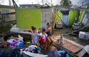En esta imagen del sábado 14 de octubre de 2017, Arden Dragoni, segundo por la izquierda, posa con su esposa Sindy, sus tres hijos y su perro Max, rodeados por lo que queda de su casa destruida por el huracán María en Toa Baja, Puerto Rico. Foto: AP