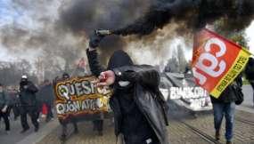 Las personas se protegen de las granadas de humo durante un día de protesta nacional contra las reformas económicas y sociales del gobierno / Fotos: AFP
