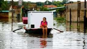 Carolina Vera, de 13 años, viaja en un bote a través de una calle inundada en el barrio de Villa Colorada, en Asunción, Paraguay