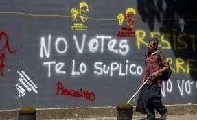Un hombre pasa junto a un grafitti contra las elecciones en una calle de Caracas, Venezuela, el sábado 14 de octubre de 2017. Foto: AP