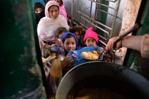 Los residentes paquistaníes reciben comida donada en un punto de distribución en el santuario de Bari Imam en Islamabad el 9 de febrero de 2017.
