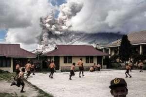 Niños de una escuela juegan mientras el volcán Monte Sinabung arroja ceniza, Sumatra del Norte, el 10 de febrero de 2017.