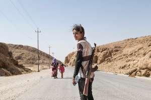 Niña Yezidi lleva un rifle de asalto para proteger a su familia de ISIL.