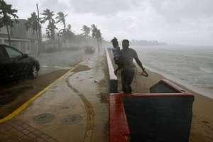 Un hombre y su hija huyen de las lluvias en una playa de San Juan, Puerto Rico, el 19 de septiembre de 2017, antes de la llegada del huracán María.