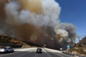 Un automóvil de la policía bloquea la autopista 241 cuando el humo del cañón 2 Fire cubre la autopista cerca de Orange, California, el 9 de octubre de 2017