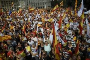 """Los manifestantes ondean banderas españolas y catalanas durante una manifestación convocada por la Sociedad Civil de Cataluña bajo el lema """"Cataluña sí, España también"""" en Barcelona el 12 de octubre de 2017"""