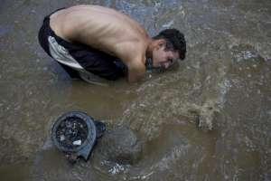 David García mantiene apenas la cabeza por encima del agua mientras rasca el fondo del contaminado río Guaire