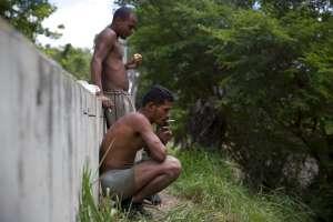 Félix Díaz fuma un cigarrillo junto a Ángel Villanueva, que come un trozo de pan durante un descanso de su jornada rascando el fondo del contaminado río Guaire