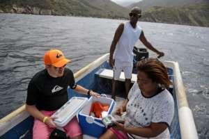 Nancy Rodríguez coloca las tarjetas de crédito de los turistas en una caja para llevarlas en un barco frente a la costa -donde puede encontrar una señal de internet