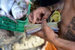 Un pescador cuenta los billetes en la playa en el pueblo de Chichiriviche de la Costa