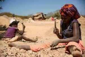 Un niño y una mujer rompen piedras extraídas de una mina de cobalto. Foto: AFP