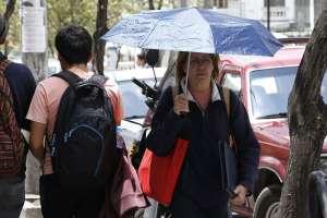 QUITO, Ecuador.- Mujer camina por las calles de la capital protegiéndose del intenso sol. Foto: API.