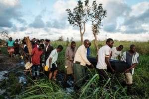 BEIRA, Mozambique.- Personas cargan el cofre de una persona fallecida tras paso de ciclón. Foto: AFP.