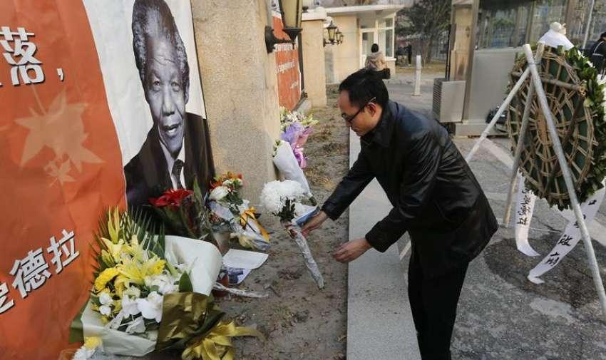 Un hombre coloca una rosa junto a una fotografía del expresidente Nelson Mandela en la embajada sudafricana en Pekín, China. Foto: EFE