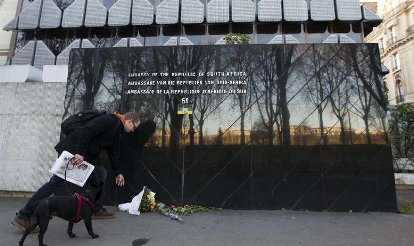 Un hombre deposita unas flores en la embajada sudafricana en París, Francia. Foto: EFE