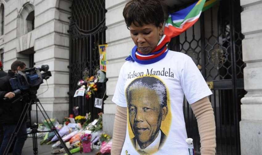 13.- Una mujer luce una camiseta con la foto del expresidente sudafricano Nelson Mandela frente a la entrada de la Alta Comisión de Sudáfrica en Londres, en Reino Unido. Foto: EFE