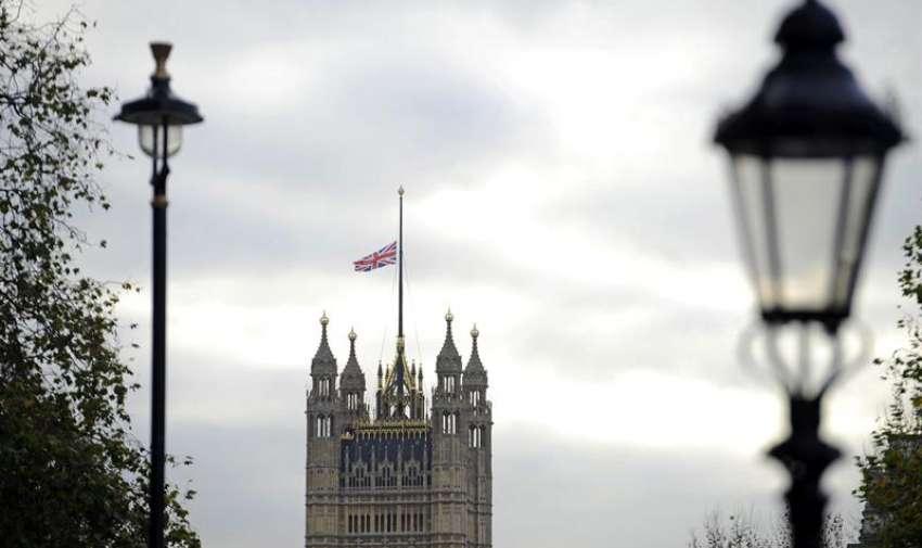 La bandera británica ondea a media asta en las Casas del Parlamento en Westminster Flores en honor al expresidente sudafricano Nelson Mandela, en Londres, Reino Unido. Foto: EFE