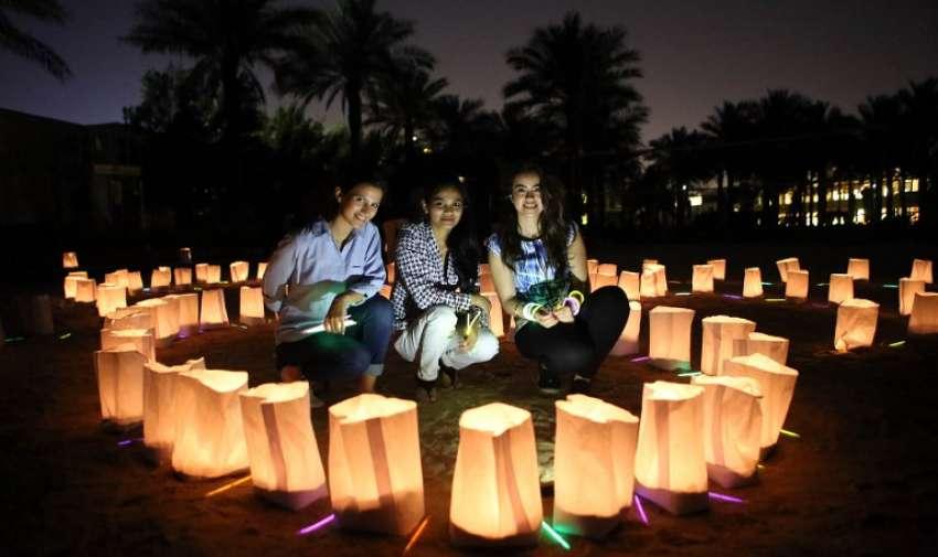 Empleados del Jumeirah Beach Hotel Messilah se sientan detrás de velas durante la Hora de la Tierra en 28 de marzo 2015 en la ciudad de Kuwait. AFP