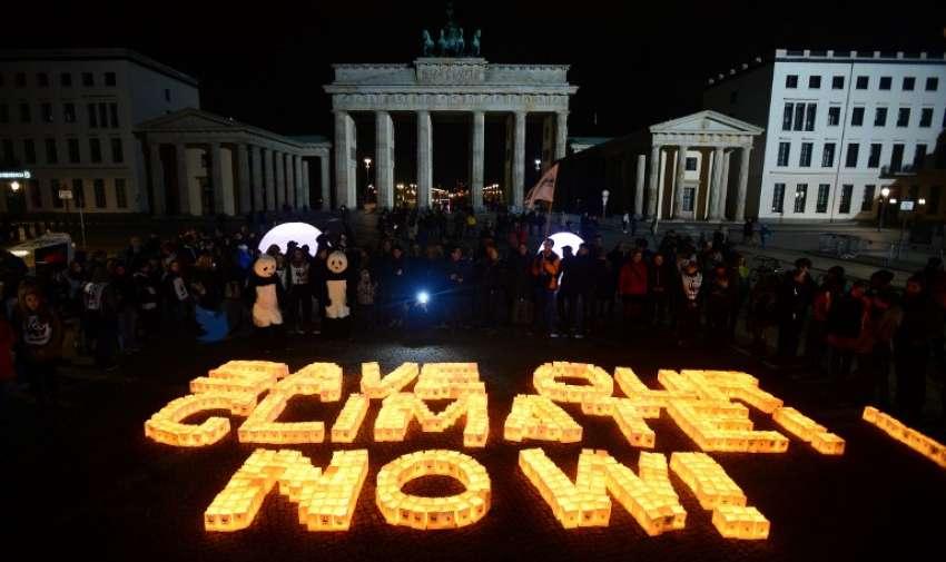"""Velas en bolsas de papel se colocan para formar las letras """" Ahorre nuestro clima , ahora"""" en frente de la Puerta de Brandenburgo en Berlín durante la campaña de sensibilización del cambio climático global """" La Hora del Planeta """" en 28 de marzo 2015. AFP"""