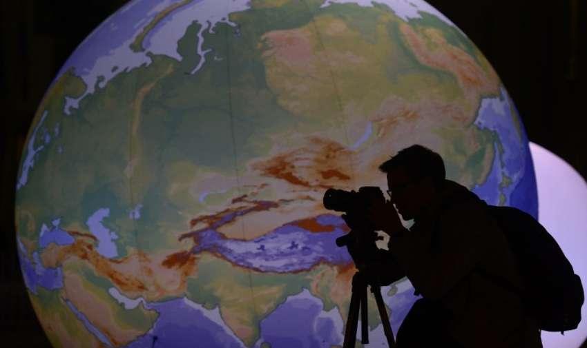 """Un fotógrafo es retratado con el fondo de un globo iluminado en la Puerta de Brandeburgo en Berlín antes de la campaña de concienciación del cambio climático global """" Hora del Planeta"""" el 28 de marzo de 2015. AFP"""