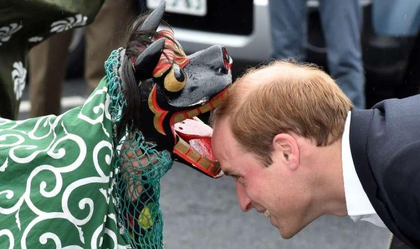 El príncipe Guillermo ( R) , duque de Cambridge , es recibido por una danza del león durante su visita a la Chime de centro comercial Esperanza en Onagawa. AFP