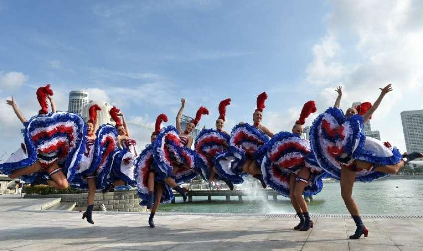 El Moulin Rouge grupo de baile de cabaret de Francia posan para fotografía,  cerca de la estatua de Merlion en Singapur el 9 de marzo de 2015. La compañía realizó en Singapur 7 de marzo en una cena de gala a la que asistieron miembros de la comunidad francesa para celebrar el Jubileo de Oro de Singapur . AFP