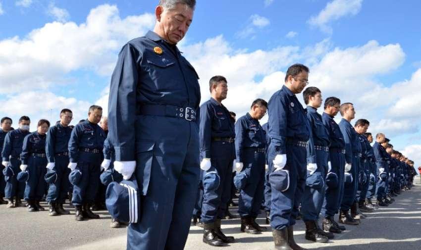 Agentes de la policía guardan un minuto de silencio por  las víctimas del terremoto y tsunami 2.011. AFP