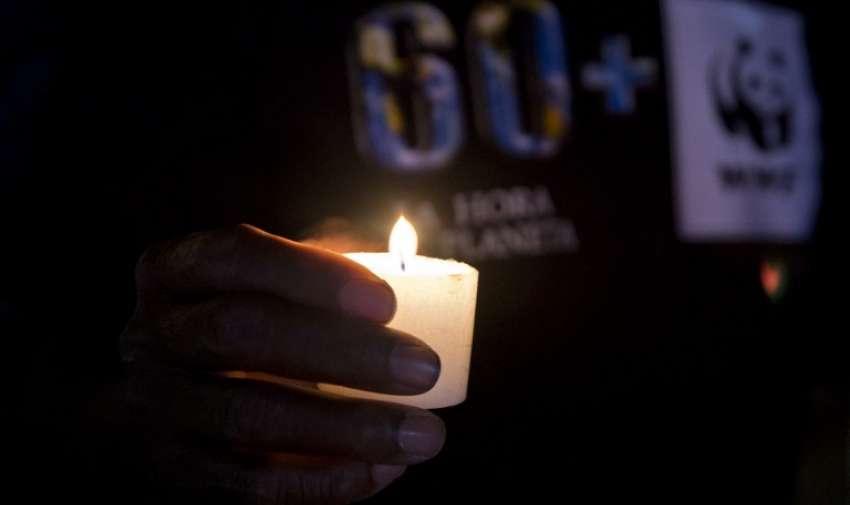 Un hombre asiste a una vigilia con velas durante la campaña La Hora del Planeta medio ambiente en el centro comercial Jardín Plaza en Cali , departamento del Valle del Cauca , Colombia , el 28 de marzo de 2015. AFP