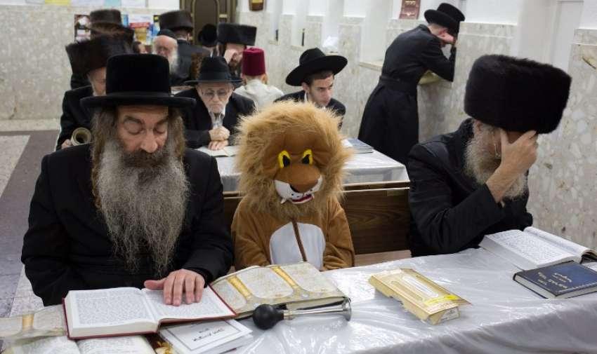 Judios ultra-ortodoxos y un niño disfrazado en una sinagoga en la ciudad israelí de Bnei Brak , cerca de la ciudad costera de Tel Aviv el 04 de marzo 2015 durante la fiesta de Purim. AFP