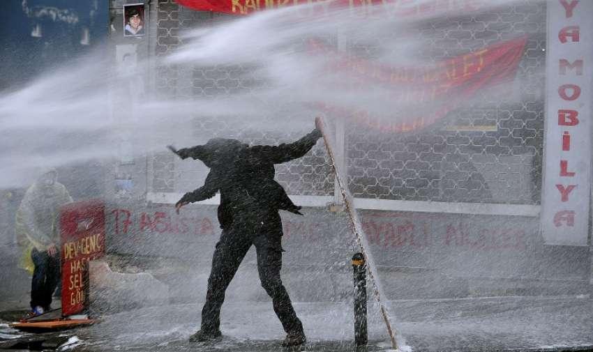 Un manifestante sostiene una tabla para esconderse de un cañón de agua de la policía el 11 de marzo de 2015, de Estambul, durante los enfrentamientos a raíz de una protesta en la memoria de un adolescente muerto en 2013. AFP