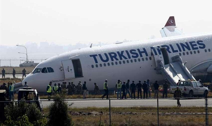 Miembros de los servicios de emergencia inspeccionan un airbus de Turkish Airlines después de que se saliera de la pista al aterrizar en el aeropuerto internacional de Katmandú (Nepal). EFE