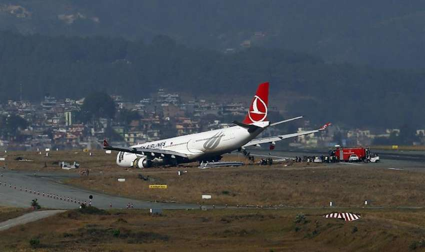 Miembros de los servicios de emergencia inspeccionan un airbus de Turkish Airlines después de que se saliera de la pista al aterrizar en el aeropuerto internacional de Katmandú (Nepal) hoy, miércoles 4 de marzo de 2015. EFE