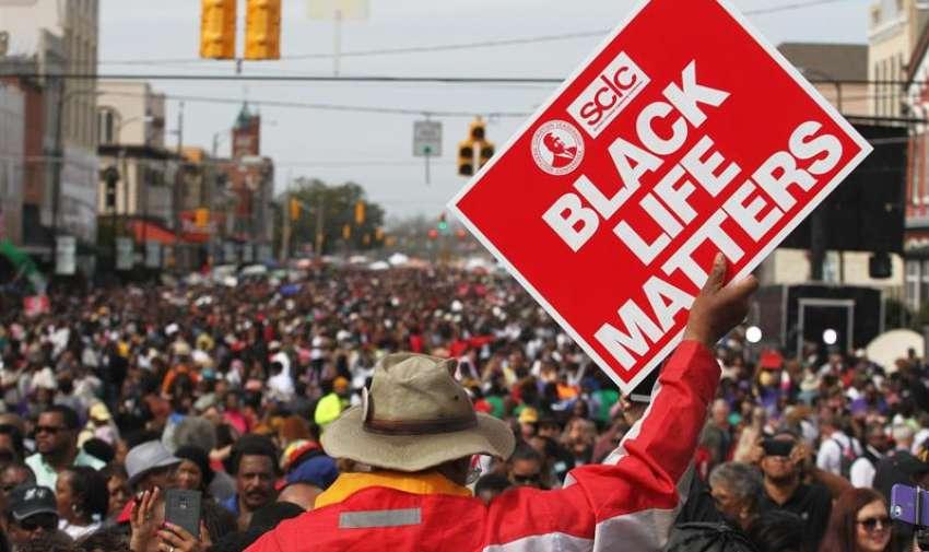 Nathan Caballero, sostiene un cartel durante la conmemoración del  aniversario 50 del cruce de la Edmund PettusBbridge el 'Domingo Sangriento' , en Selma. EFE