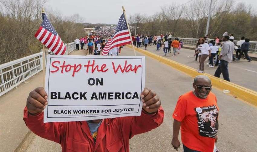 """Un manifestante sostiene un cartel de protesta al cruzar el puente Edmund Pettus durante la conmemoración del aniversario 50 por el  cruce del puente del """" Domingo Sangriento """" , en Selma, Alabama, EE.UU.  EFE"""