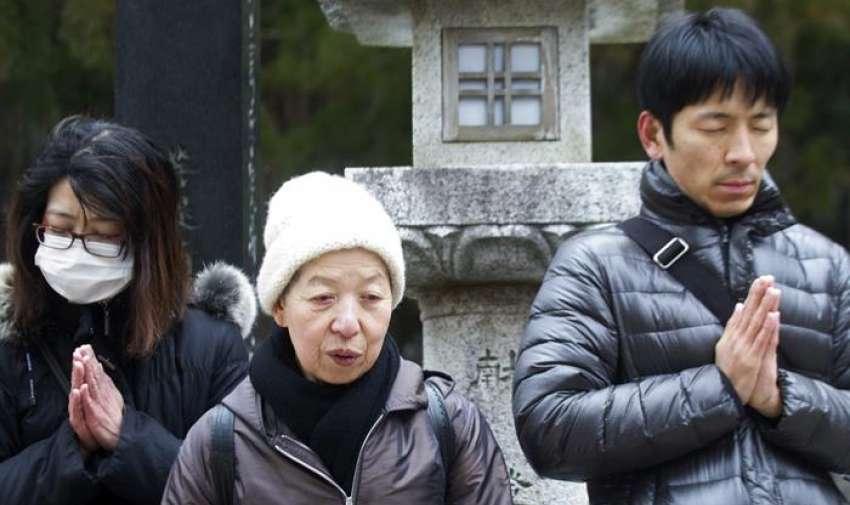 Un grupo de personas rezan por las víctimas del terremoto y posterior tsunami de 2011, en el Monte Koya (Japón)