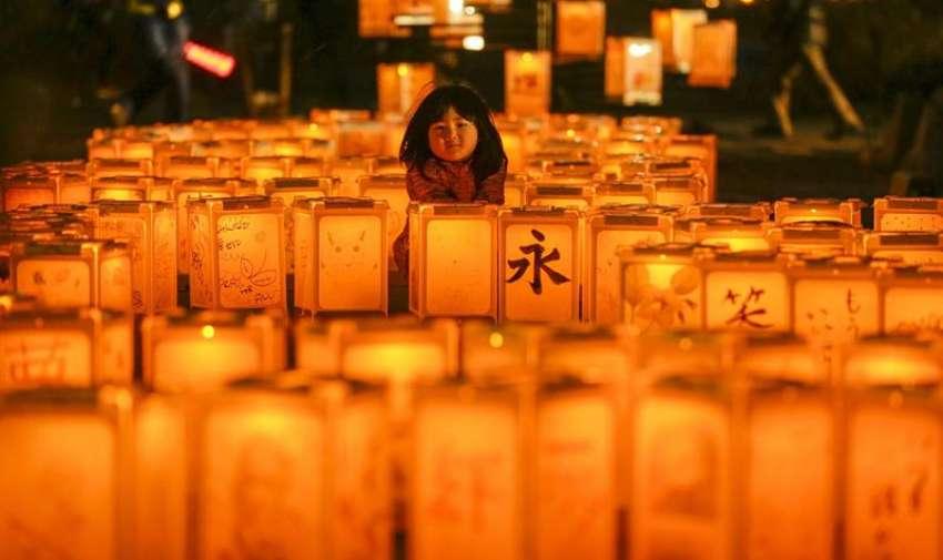 Una niña posa junto a varias linternas encendidas por las víctimas del terremoto y posterior tsunami de 2011 en el instituro Yuriage en Natori, en la prefectura de Miyagi al norte de Japón hoy, miércoles 11 de marzo de 2015. EFE