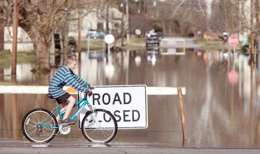 Un niño monta su bicicleta cerca de la inundación  del río Ohio en New Richmond , justo al este de Cincinnati, Ohio, EE.UU. foto tomada el 15 de marzo de 2015. EFE