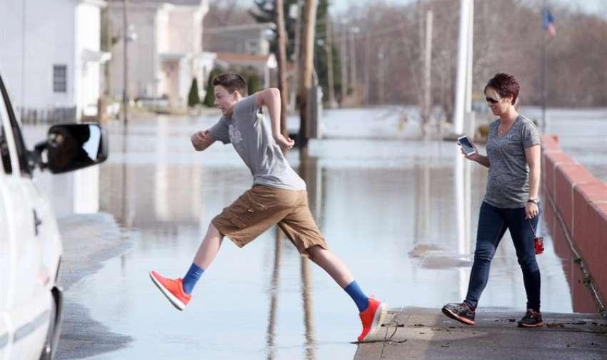 Uno de los moradores del sector, Jackie Frazie, da un gran salto para evitar mojarse por las calles inundadas. Foto: EFE