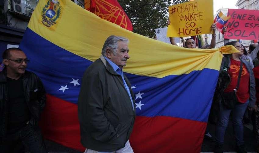 El expresidente de Uruguay, José Mujica (c), camina frente a una bandera de Venezuela. EFE