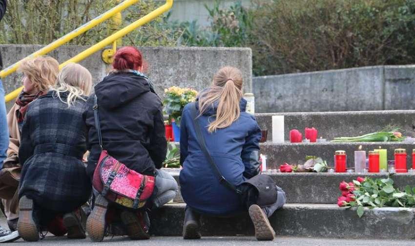 Varios estudiantes encienden velas y dejan flores en memoria de los fallecidos en el accidente aéreo de los Alpes franceses, frente al colegio Joseph-König de Halter am See, Alemania. EFE