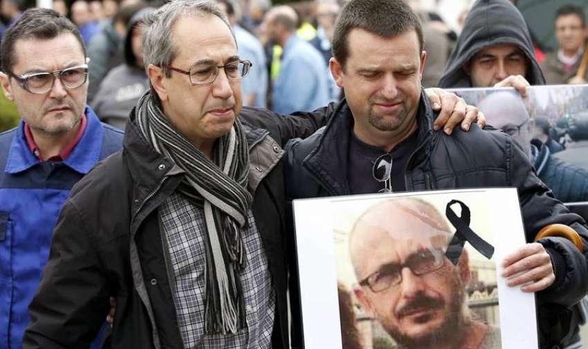 Trabajadores de la multinacional Delphi, dos de cuyos empleados viajaban en el avión siniestrado en Francia, muestran fotografías de sus compañeros fallecidos, durante los cinco minutos de silencio en la factoría de la empresa en Sant Cugat del Vallés (Barcelona). EFE