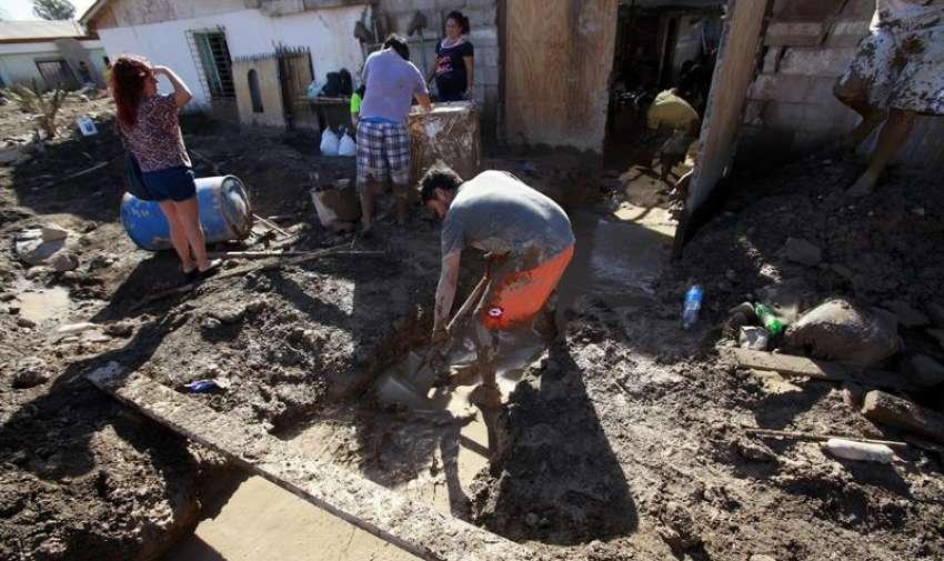 Vecinos drenan el agua de una casa afectada por las inundaciones hoy, sábado 28 de marzo de 2015, en la población de Diego de Almagro (Chile). EFE