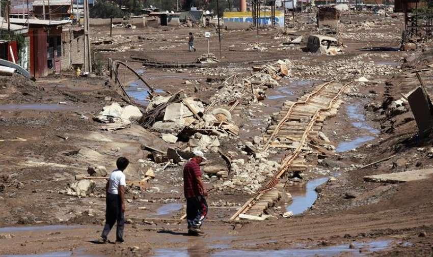 Vecinos caminan por una calle afectada por las inundaciones hoy, sábado 28 de marzo de 2015, en la población de Diego de Almagro (Chile). EFE