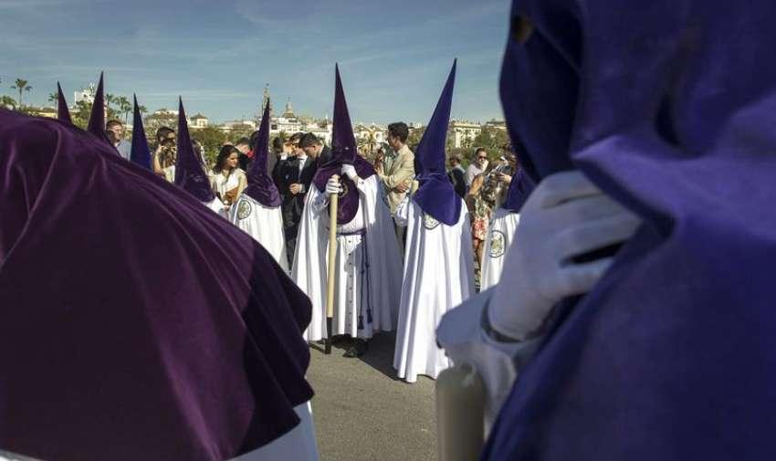 Nazarenos de la Hermandad de La Estrella pasan por el puente de Triana durante su recorrido procesional del Domingo de Ramos en Sevilla. EFE