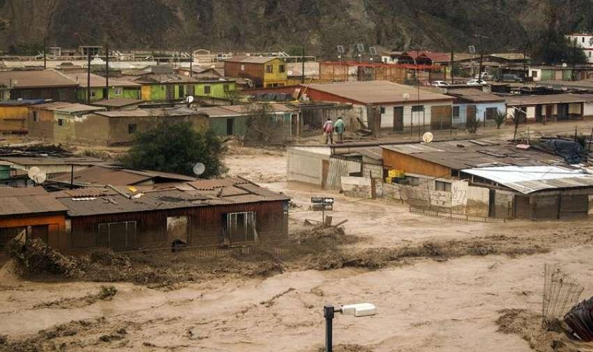 Fotografía del 25 de marzo de 2015 que muestra a dos hombres subidos en el tejado de una casa durante las ríadas que afectaron a la localidad de Diego de Almagro a 1000 kilómetros al norte de Santiago de Chile. EFE